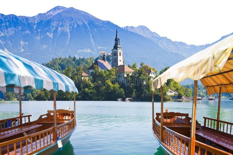 Typiska träfartyg, i slovenian kallade Pletna, i den blödde sjön, den mest berömda sjön i Slovenien med ön av kyrkan fotografering för bildbyråer