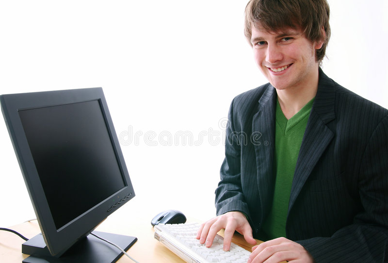Typist smile. Young businessman student or office worker typing on keyboard smiling to camera. Blank computer screen - ready for adding your own message or image royalty free stock photos