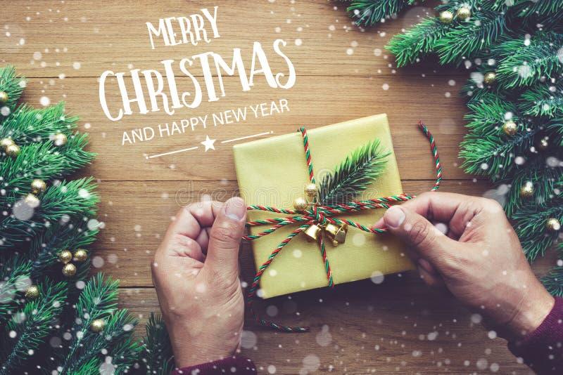 Typografi för GLAD JUL OCH för LYCKLIGT NYTT ÅR, text med den mänskliga handen som dekorerar gåvor för gåvaask royaltyfri bild