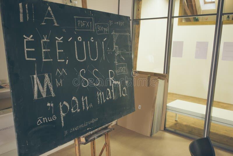 Typografielektion mit Tafel mit handgeschriebenen Kreidebuchstaben lizenzfreie stockbilder