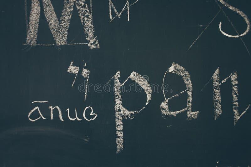 Typografielektion mit Tafel mit handgeschriebenen Kreidebuchstaben stockfotos