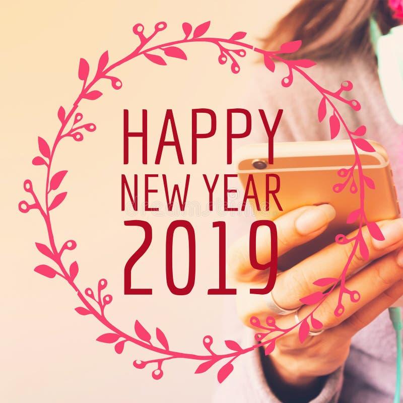 Typographie 2019 de bonne année sur l'image de la femme employant le pH mobile image libre de droits