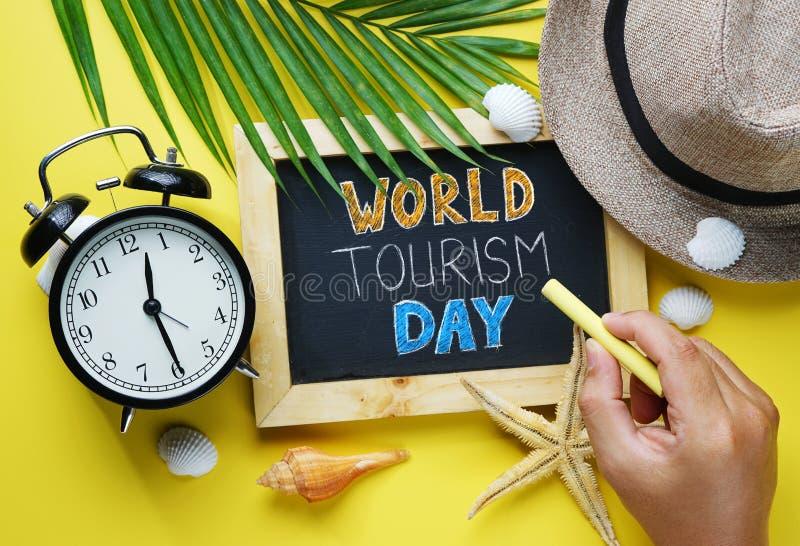 Typographie de jour de tourisme du monde Main tenant la craie jaune et le Blac images stock