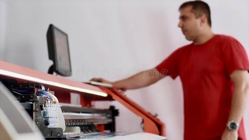 Typography operator is printing production on computerized printing press. stock photography