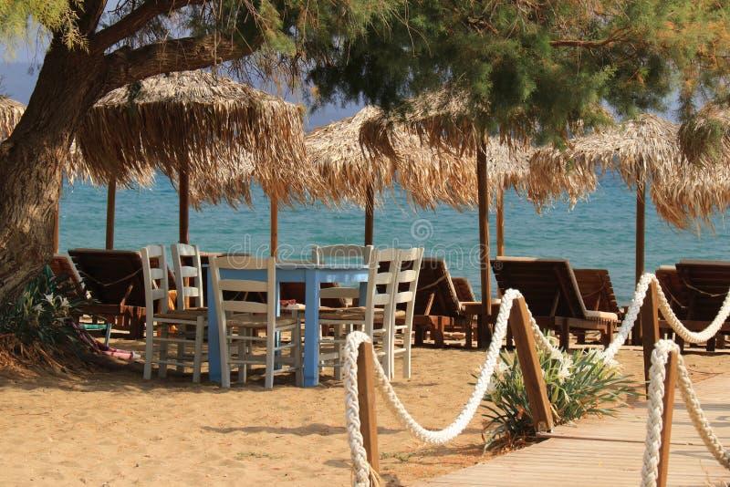 Typowa grecka scena przy kalyves wyrzucać na brzeg z drewnianymi krzesłami i stołem obraz stock