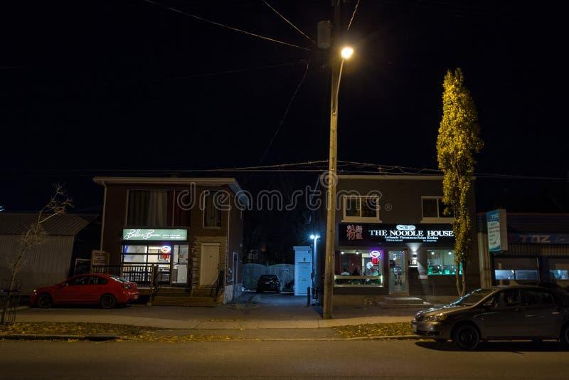 Typowi p??nocnoameryka?scy drewniani domy w mieszkaniowej ulicie w jesieni w Ottawa, Ontario, podczas jesieni nocy z samochodami  zdjęcia royalty free