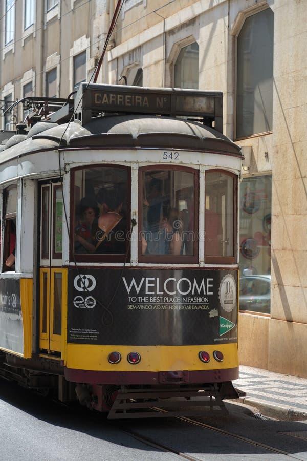 Typowy Żółty rocznika tramwaj w Wąskiej ulicie Lisbon, Portugalia zdjęcie royalty free
