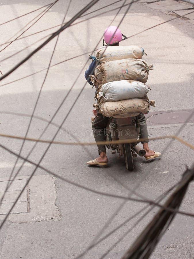 Typowy Hanoi; Mężczyzna z ciężkim ładunkiem na hulajnoga jedzie przez Han obraz royalty free