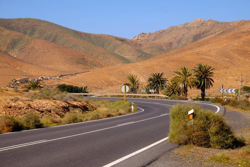 Typowy krajobraz z wyginającą się drogą i czerwonymi powulkanicznymi górami na wyspie kanaryjskiej Fuerteventura, Hiszpania zdjęcia stock