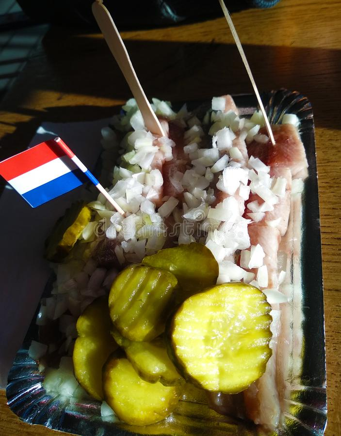 Typowy naczynie Amsterdam Holenderski śledziowy surowy, świeży, świeżo złapany, słuzyć wraz z plasterkami ogórek i kawałki biały  zdjęcie stock