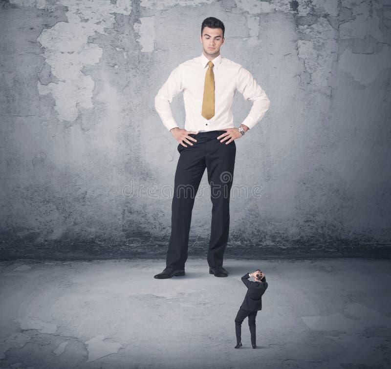 Tyrann des großen Geschäfts, der kleinen Mitarbeiter betrachtet stockfotografie