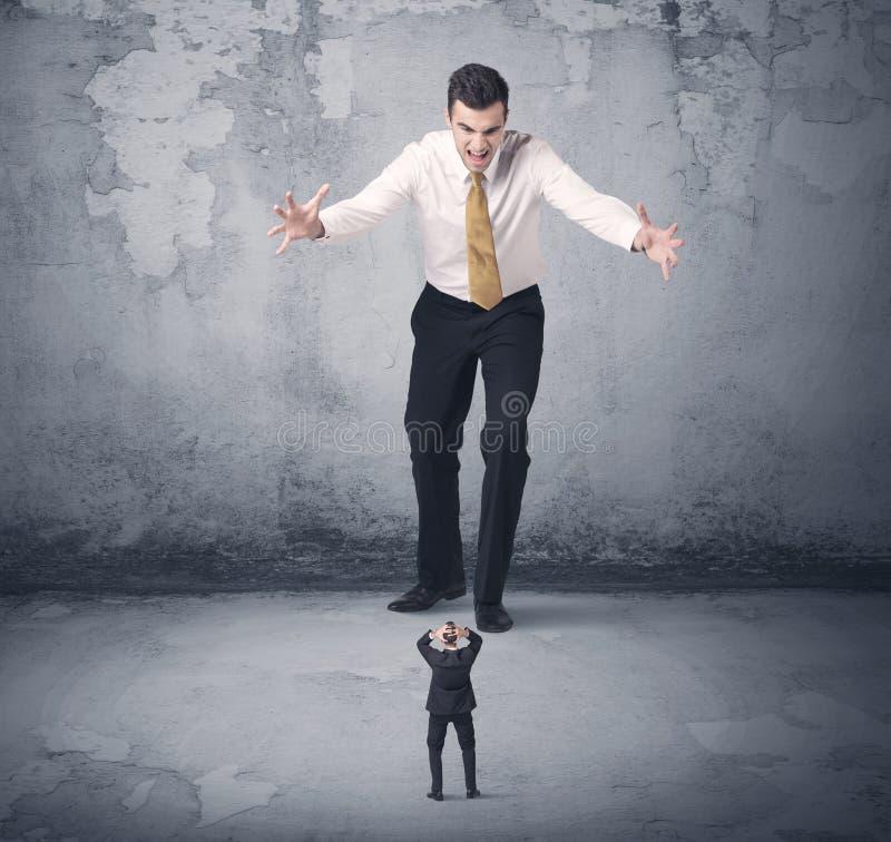 Tyrann des großen Geschäfts, der kleinen Mitarbeiter betrachtet lizenzfreie stockbilder