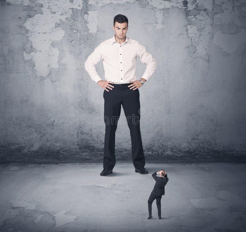 Tyrann des großen Geschäfts, der kleinen Mitarbeiter betrachtet stockbilder