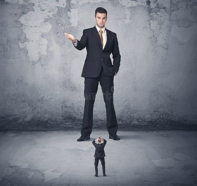 Tyrann des großen Geschäfts, der kleinen Mitarbeiter betrachtet stockfoto