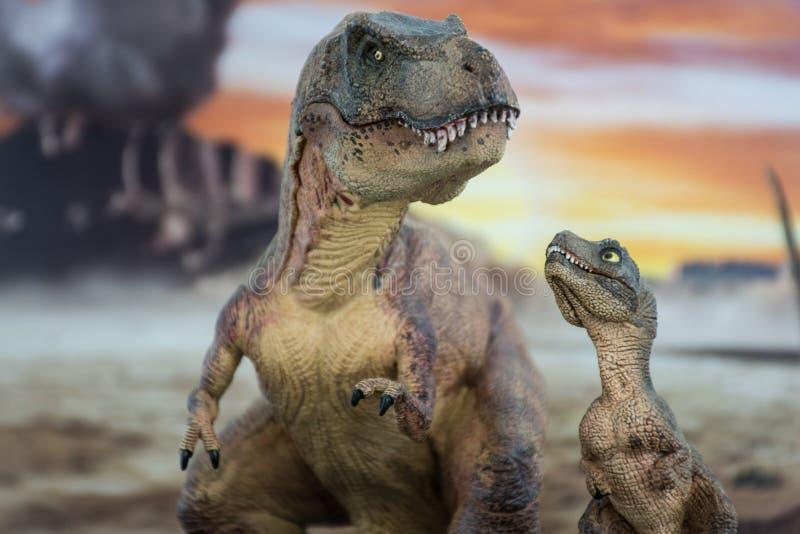 Tyrannosaurus rex met baby t -t-rex met krijtachtig land op de achtergrond stock foto