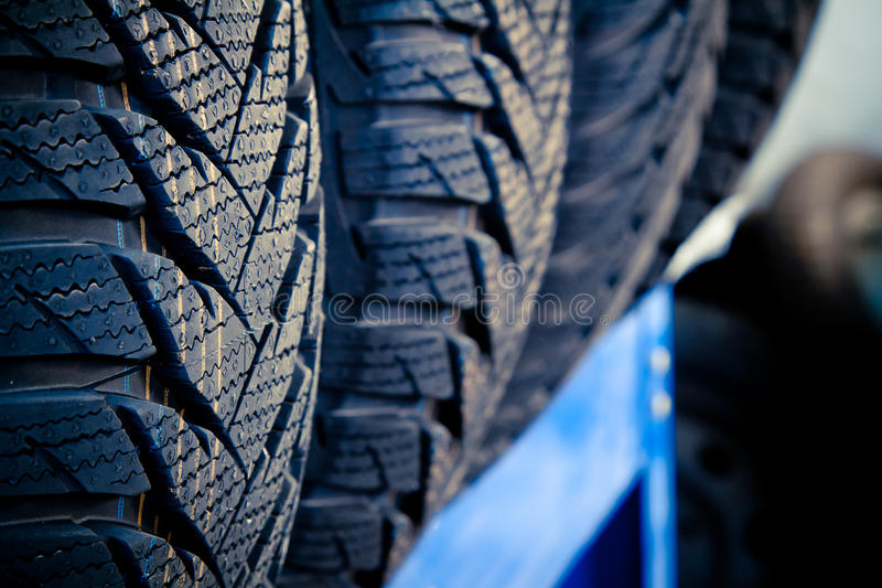 Tyre close up. Close up on a row of brand–new tyres in an auto repair shop. Selective focus on first tyre. Copy space. No brand names on tyres. Slight cross stock photography