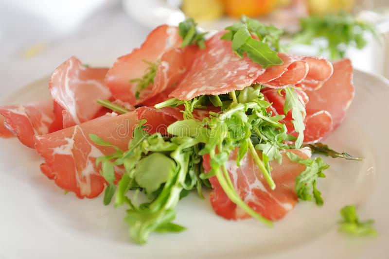 Tyrolean bacon slices and arugula in a dish stock images