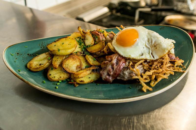Tyrolean fried potatoes with meat bacon, mushrooms and a fried egg royalty free stock image