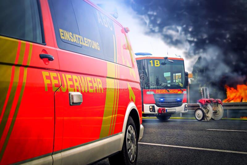 Tysk brandbekämpning åker lastbil ställningar på en gata nära en brand royaltyfri foto