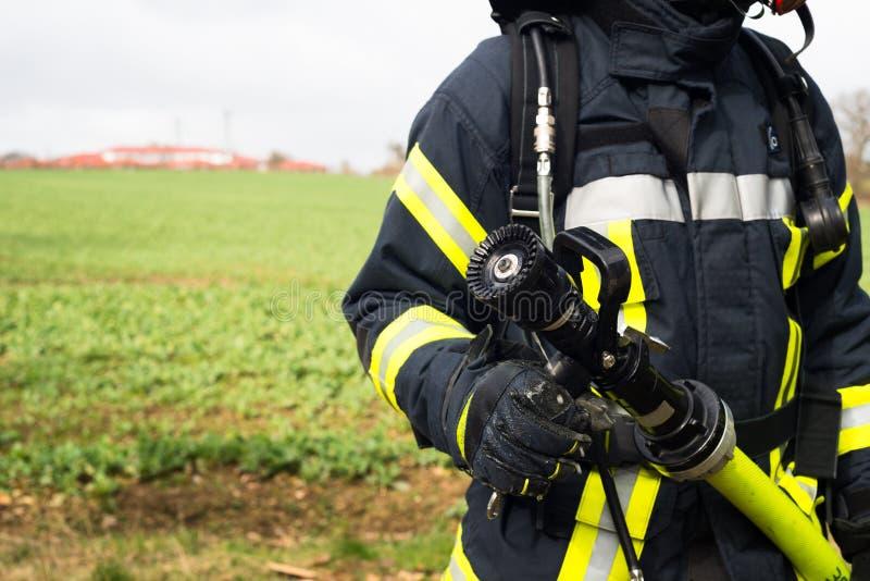 Tysk brandman med vattenslangen i handling royaltyfri foto