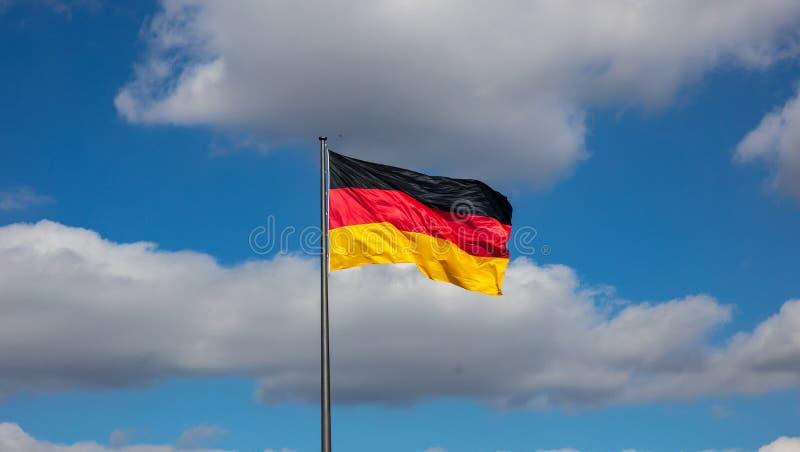 Tysk flagga som vinkar på en flaggstång mot blå himmel med moln, fotografering för bildbyråer