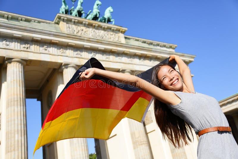 Tysk flaggakvinna som är lycklig på Berlin Brandenburg Gate royaltyfria foton