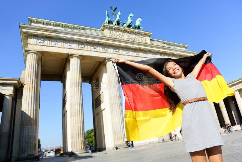 Tysk flaggakvinnaglädje på Berlin Brandenburger Tor royaltyfri fotografi