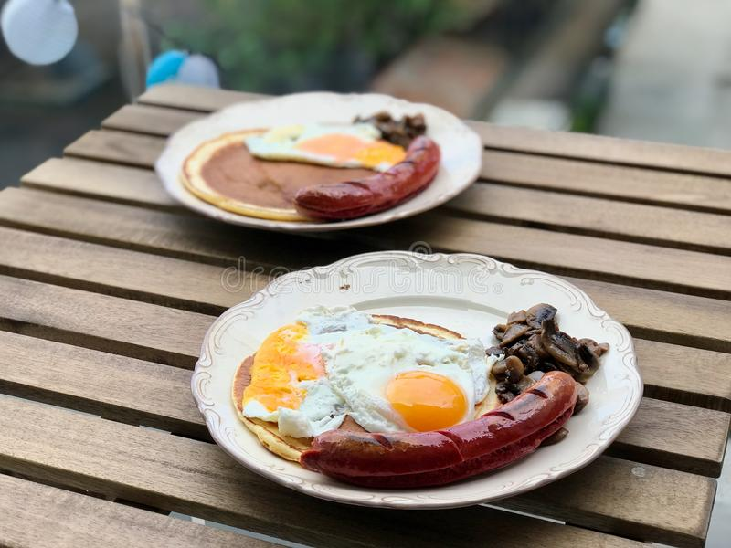 Tysk frukost för Bratwurstkorv med pannkakan, Fried Eggs, frasig bacon och champinjoner royaltyfri bild