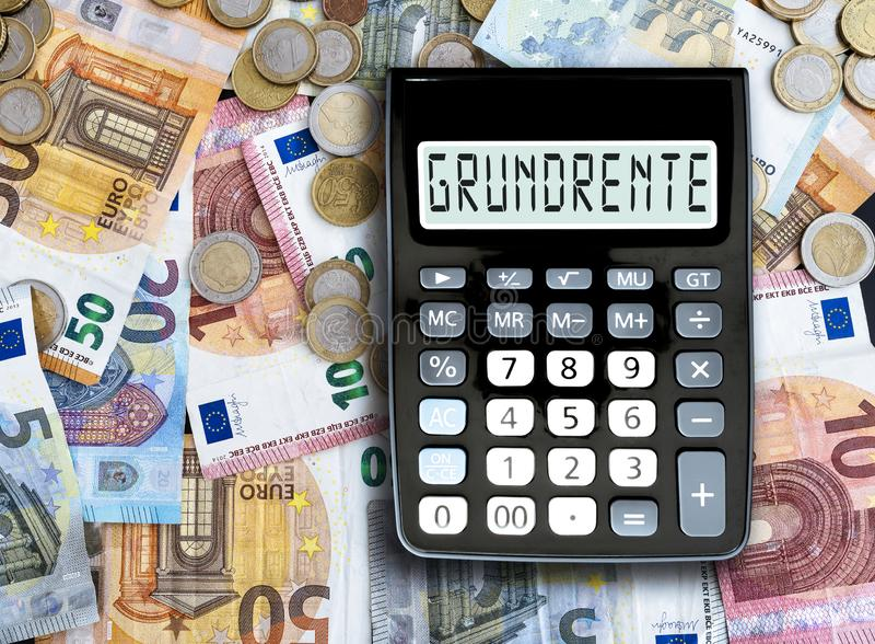 Tysk grundläggande pension för ord som GRUNDRENTE är skriftlig på skärm av miniräknaren mot kassapengar på tabellen arkivfoton