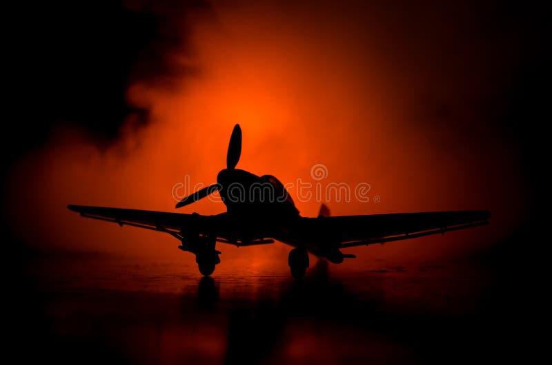 Tysk jetdriven modellnivå för bilskrälle (Ju-87) i besittning Mörker - orange brandbakgrund Krigplats Selektiv fokus (skillnad royaltyfri fotografi