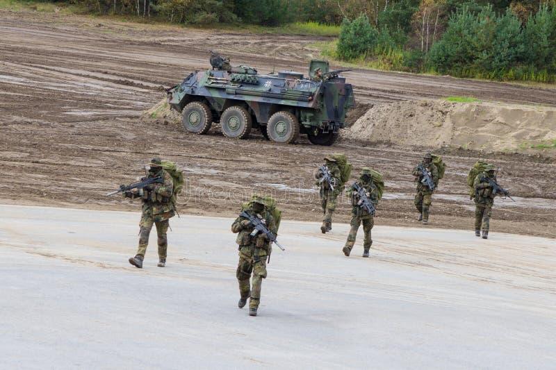 Tysk Ksk, specialförbandkommando går över en plattform nära slagfältet royaltyfri foto