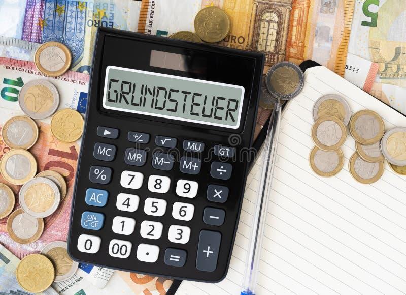 Tysk ordGrundsteuer fastighetsskatt eller landskatt på skärm av miniräknaren med euroräkningar och mynt i bakgrund arkivfoto