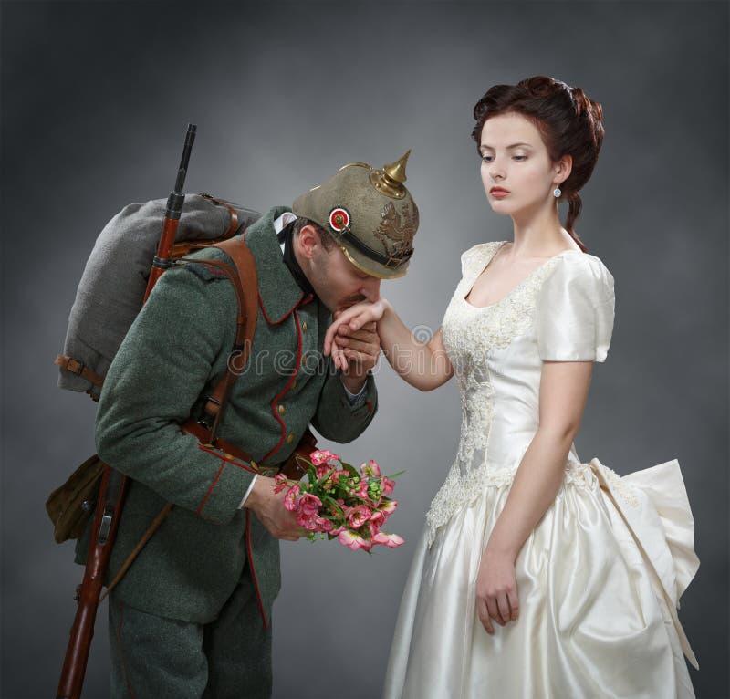 Tysk soldat som kysser en dams hand arkivbilder