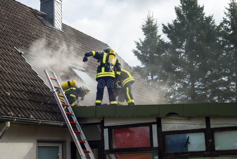 Tyska brandmän i handling med syrecylindrar royaltyfri fotografi