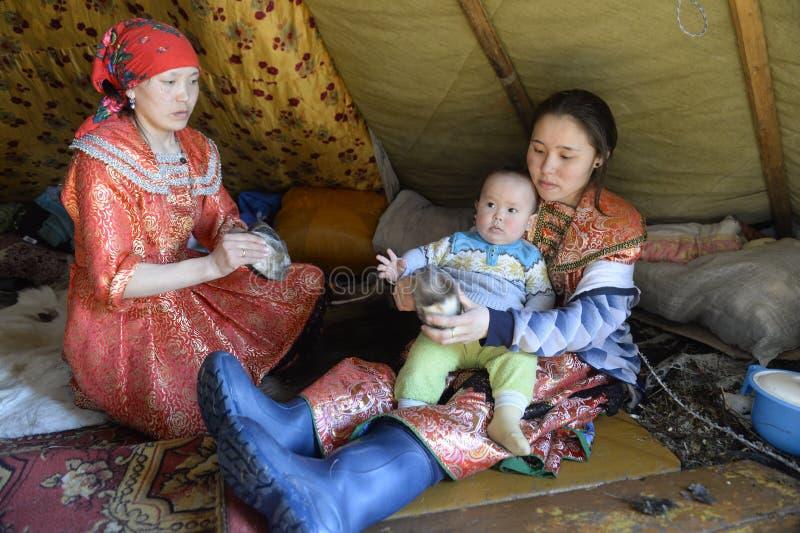 Tyska kvinnor för ryska arktiska infödda kvinnor med barn i lägenhethuset - epidemin! royaltyfri foto