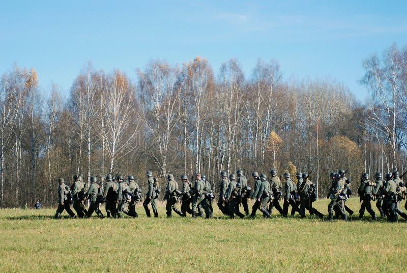 Tyska soldater-reenactors går med vapen arkivfoto