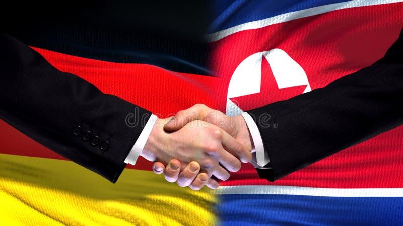 Tyskland- och Nordkorea handskakning, internationellt kamratskap, flaggabakgrund arkivfoto
