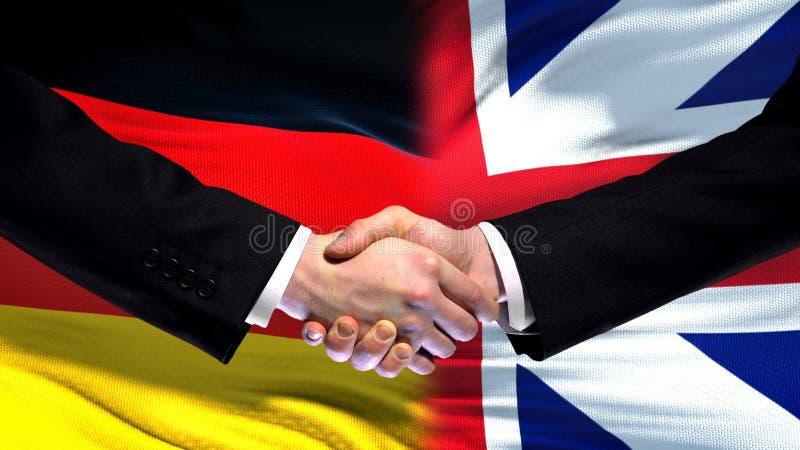 Tyskland- och Storbritannien handskakning, internationellt kamratskap, flaggabakgrund arkivfoto