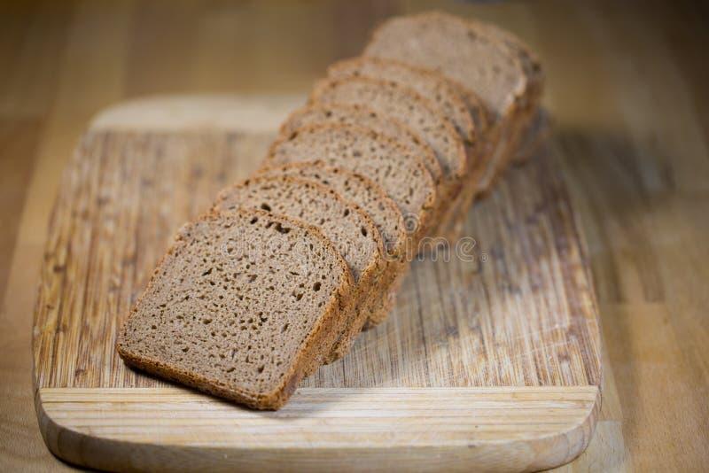 Tyskt bröd, helt korn på träbräde arkivfoton