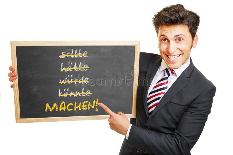 Tyskt motivationbegrepp på svart tavla royaltyfri bild