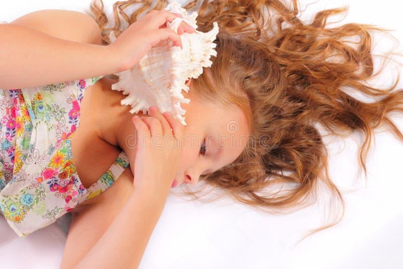 Tyst liten flicka med snäckskalet royaltyfria bilder