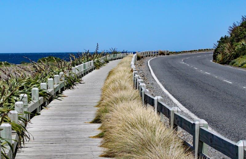 Tyst och fridsam kustväg och trästrandpromenad nära gummistöveln, Nya Zeeland arkivbild