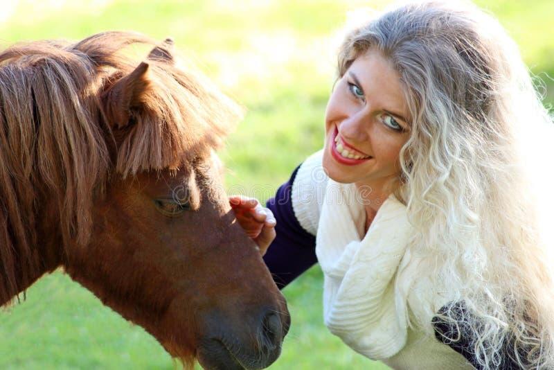 Tystar ned den kastanjebruna ponnyn för roliga blonda flickaslaglängder, den soliga dagen royaltyfria foton