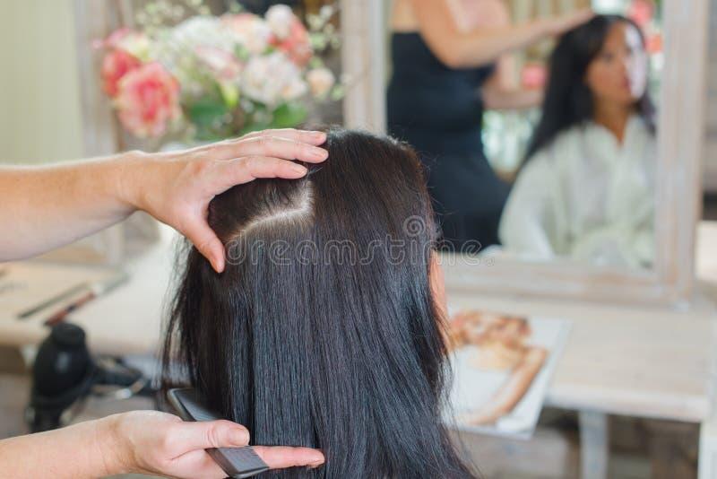 Tytułowanie kobiety ` s włosy w salonie zdjęcia stock