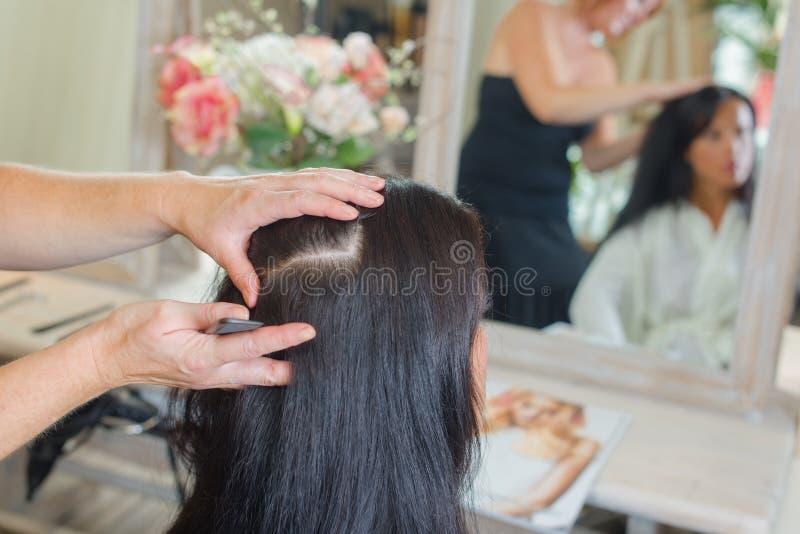 Tytułowanie kobiety ` s włosy w salonie fotografia stock