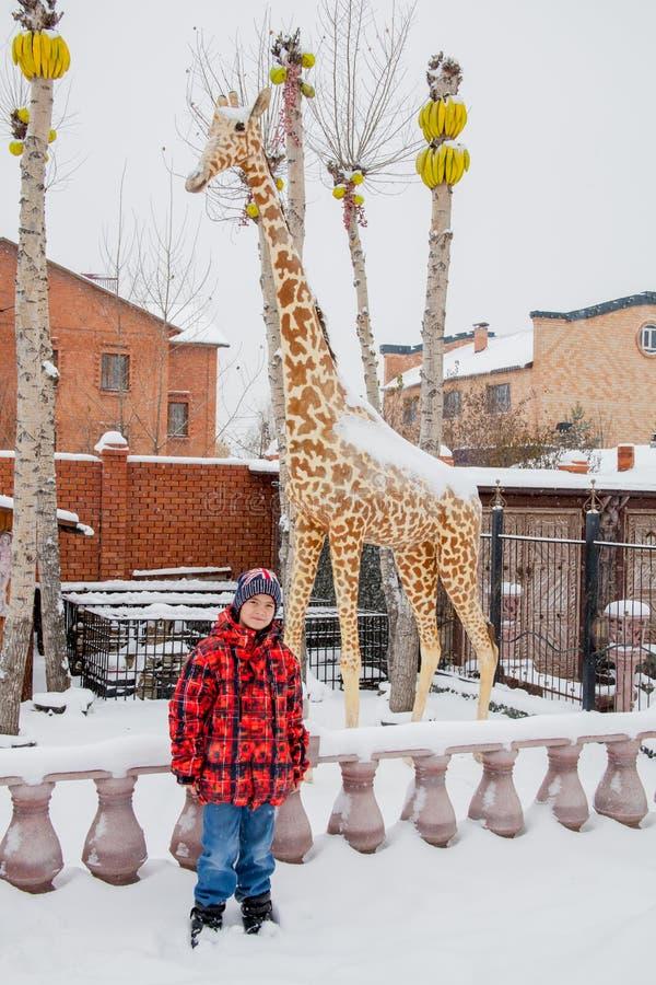 Tyumen, Rússia - menino perto de uma escultura de um girafa imagens de stock royalty free