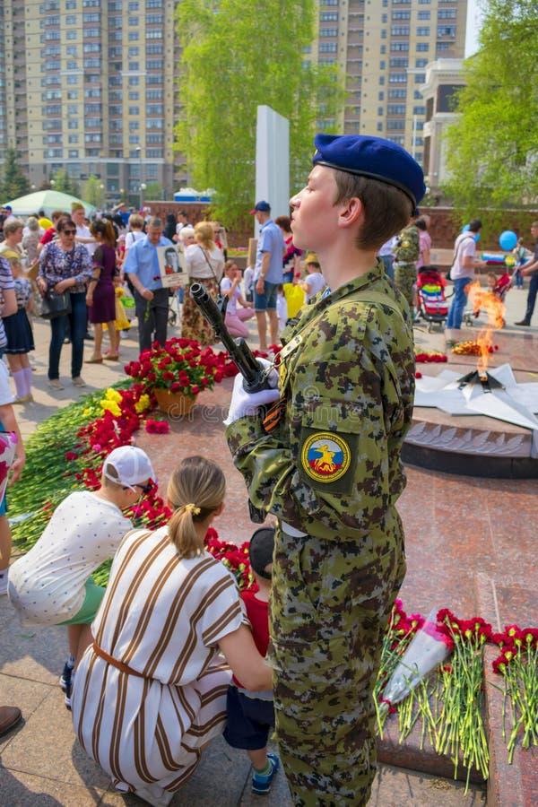 TYUMEN, RUSIA - 9 DE MAYO DE 2019: Madre que se aflige del monumento y guerrero joven Llama eterna foto de archivo
