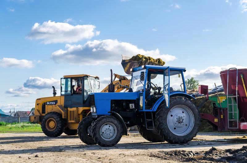 Tyumen, Rusland - Augustus 6, 2017: Een universele lader laadt de gesleepte strovoeder voor het koken van koeien stock foto