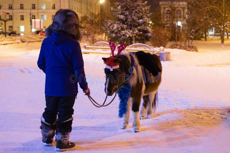 Tyumen, Russia - December 29, 2019: Man with little pony wearing red deer horns, Santa Claus red hat and Christmas decorations. royalty free stock photo