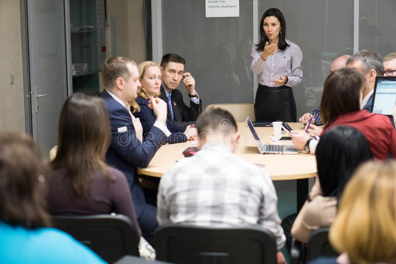 Tyumen, Russie, 02 21 2017 Directeur féminin présent le rapport parlant au chef indou de travailleur d'équipe diverse tenant l'ex photographie stock